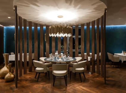 Circular Dining Area With Wood Partition, Seating For Six at Round Table Under Chandelier in Restaurant Gold