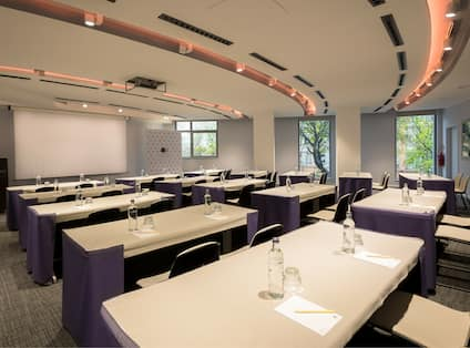 Classroom Setup in Paris Meeting Room With Tables and Chairs Facing Presentation Screen, Overhead Projector, Podium, and Windows