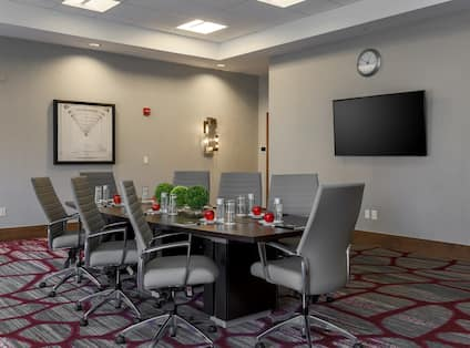 Wall Art, Entry, Wall Clock, TV, and Seating for 8 at Boardroom Table