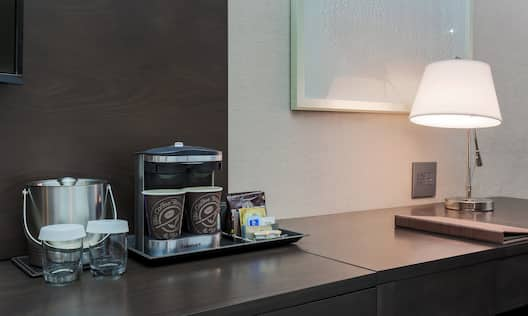 Detailed View of Hospitality Center With Ice Bucket, Coffee Maker and Cups, Desk With Illuminated Lamp