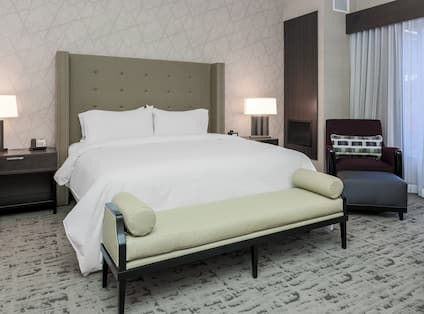 Bed Bench, King Bed, Side Tables With Illuminated Lamps, Brown Armchair, Ottoman and Window With Long Drapes in Junior Suite