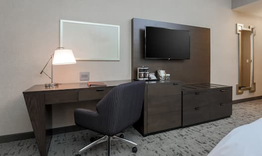 Whiteboard Above Work Desk With Illuminated Lamp, Hospitality Center, TV, and Full Length Mirror in King Room