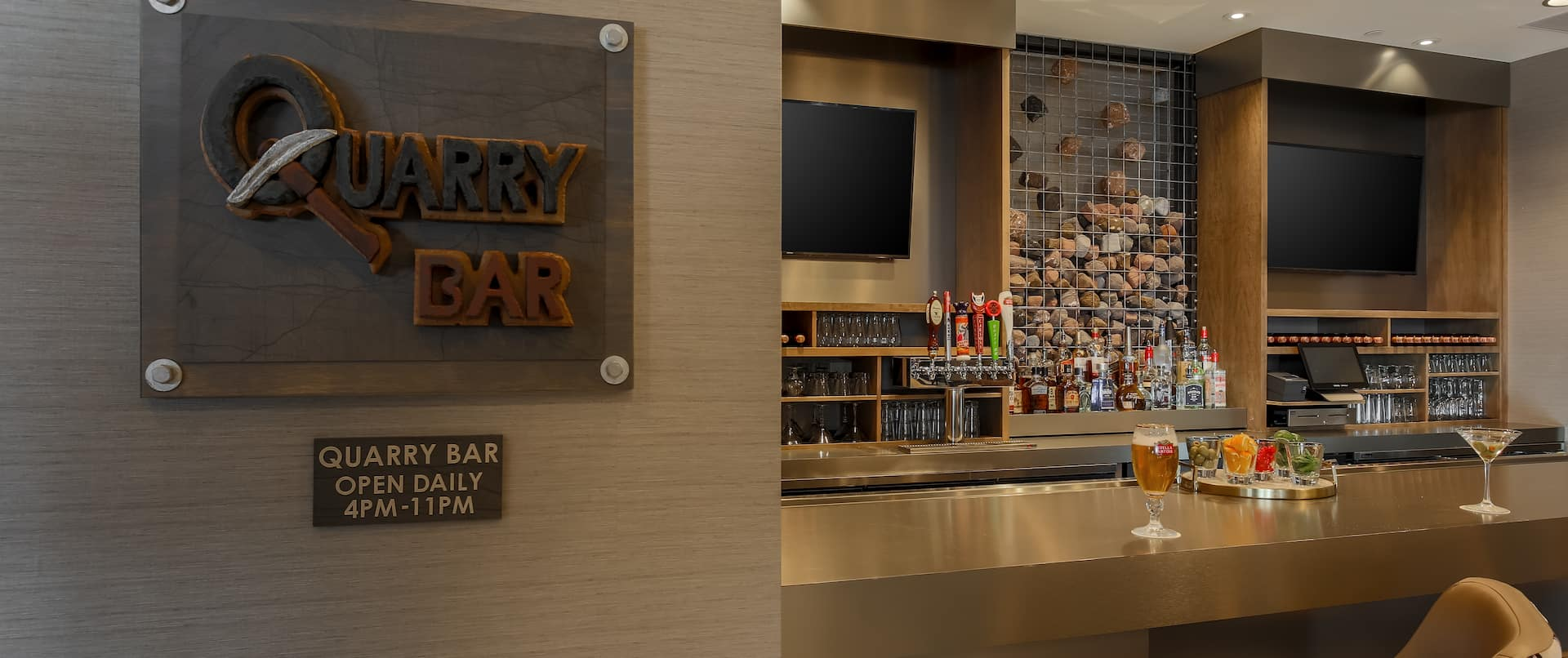 Detailed View of Quarry Bar and Hours of Operation Signage With View of TVs and Seating at Counter With Cocktails and Fully Stocked Bar
