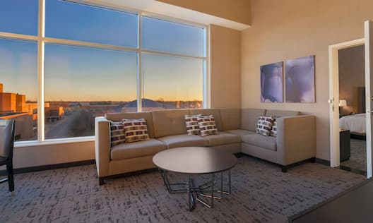 Large Window With Sunset View, Sectional Sofa, Round Coffee Table, Wall Art, and Open Doorway to Bedroom in Corner Suite Living Area