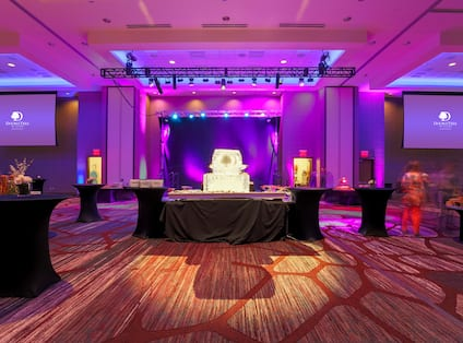Dramatically Lit Ballroom Set Up for Wedding Reception With Two Large Projector Screens, Performance Stage and Black Cocktail Tables