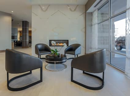 Round Coffee Table, Four Black Chairs, Fireplace and Large Window With Open Drapes in Lobby Lounge Area