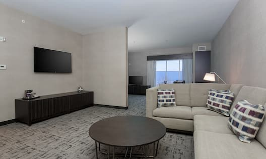 Living Area With Illuminated Floor Lamp, Sectional Sofa, Coffee Table, TV and View Toward Bedroom Window With Open Drapes in King Suite