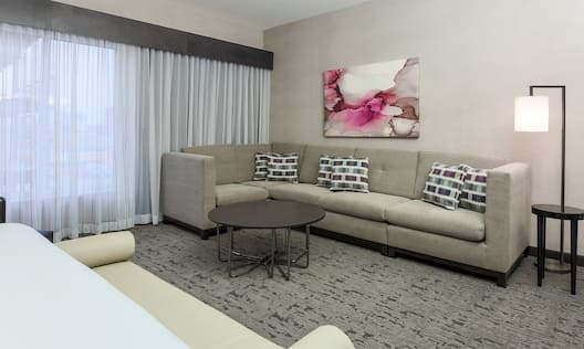 Bed Bench, King Bed, Window With Sheer Drapes, Coffee Table, Wall Art Above Sectional Sofa, and Illuminated Floor Lamp in Junior Suite