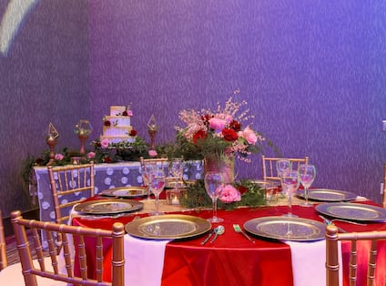 Chairs, Tables With Place Settings, White Napkins, and Flowers on Red Linens and Table With Candles and Wedding Cake in Ballroom Set Up for Wedding Reception