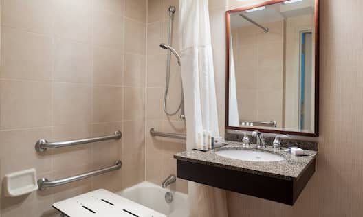 Accessible Bathtub With Shower Seat, Grab Bars and Handheld Showerhead, Vanity Mirror, Sink, and Towels