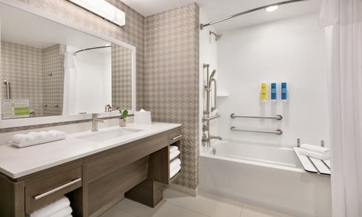 Spacious accessible bathroom featuring tub with seat vanity and mirror
