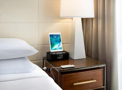 Close Up of Smartphone and Tablet Charging on Bedside Table in Guest Room