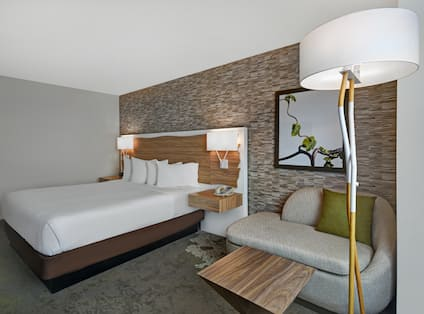 guest room with bed and lounge chair