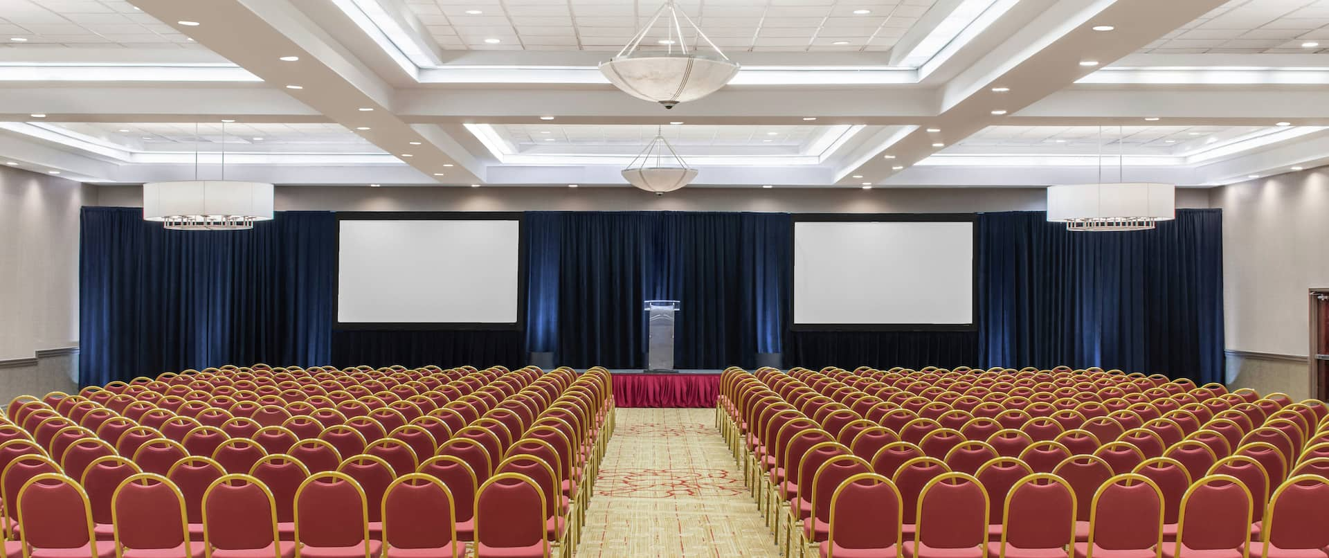 rows of chairs facing presentation screens in a conference room