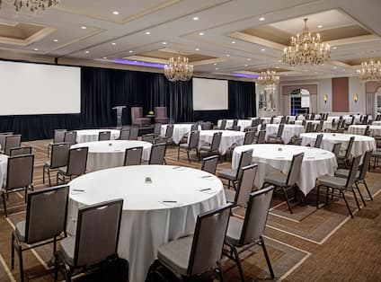 Ballroom with Banquet Tables, Stage and Two Screens