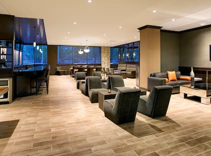 Overview of Windows With Night View, Cocktail Tables, and Lounge Seating by TV in Hudson Grille