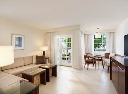 Living area, dining table with two chairs and a bench, and outdoor patio in the Ocean View Suite with Lanai Patio
