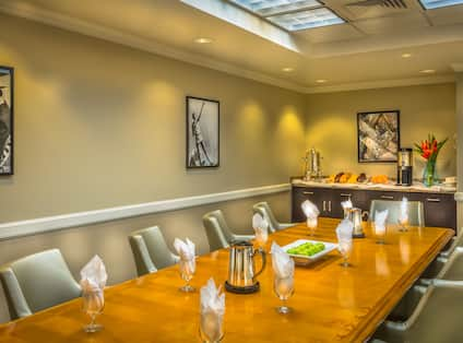 Wall Art, Refreshment Area, Chairs Around Large Table With White Napkins in Drink Glasses, Two Water Pitchers and White Tray of Green Apples in Vignette Boardroom