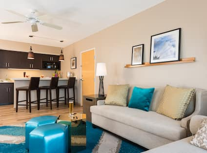 Suite Living Room With Ceiling Fan, Wall Art, Lamps, Soft Seating, and Kitchen With Counter Seating and Microwave