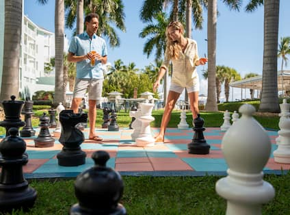 A couple enjoying a large chess game outdoors