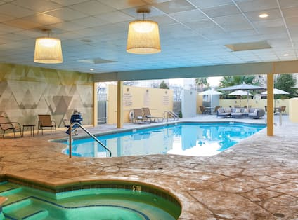 Covered Pool and Whirlpool  With Tables, Chairs and Tables With Sun Umbrellas on Outdoor Patio