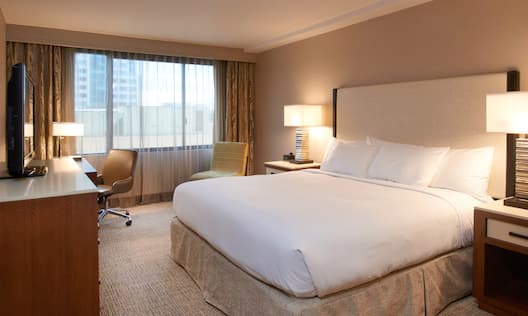 King Bed, Illuminated Lamps on Bedside Tables, TV, Work Desk, Window With Sheer Drapes, and Armchair in Corner of Accessible Guest Room