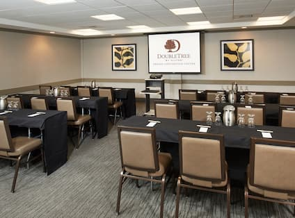 Classroom Setup in Tioga Meeting Room with Tables and Chairs Facing Audio/Visual Equipment Table, Wall Art, and Presentation Screen