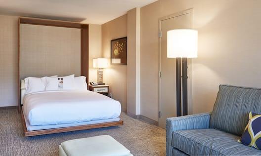 Murphy Bed, Illuminated Lamp on Bedside Table, Wall Art, Entry Door, Illuminated Floor Lamp, Blue Sofa, and Ottoman