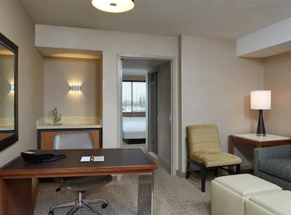 Executive Suite Seating Area With Wall Mirror Above Work Desk, Wet Bar, Open Doorway to Bedroom, Chair, Illuminated Lamp on End Table, Sofa Bed and Ottoman