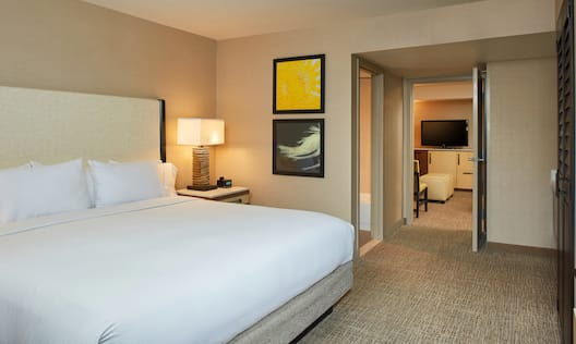 King Bed, Illuminated Lamp on Bedside Table, Wall Art, Open Doorways to Bathroom and Living Room in Executive Suite
