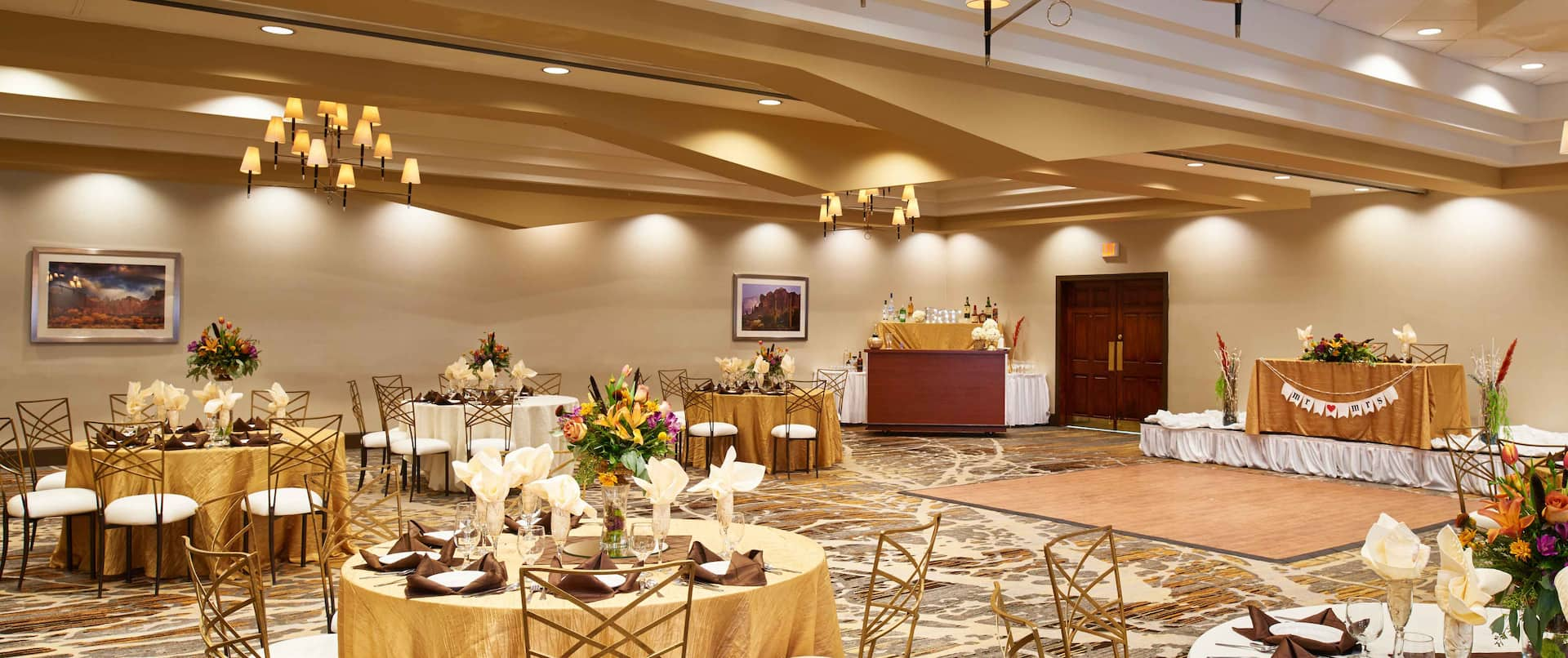 Ballroom Set Up With Place Settings and Flowers on Banquet Tables, Bar and Dance Floor