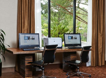 Business Center With Two Computers and Printer on Work Desk by Window With Open Drapes