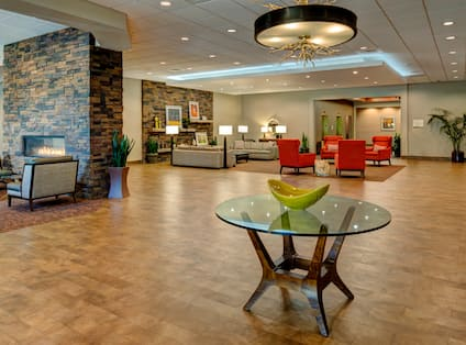 Tables, Soft Seating Around Fireplace and Additional Seating in Lobby Lounge Area With View of Front Desk