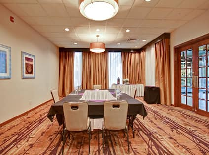 Wall Art, Table With Closed Drapes, Glass Entry Door, Drinking Glasses, and Napkins on Table With Black Linens, Refreshment Table in Meeting Room