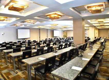 Classroom Setup in Ballroom With Wall Art, Tables and Grey Chairs Facing Presentation Screens