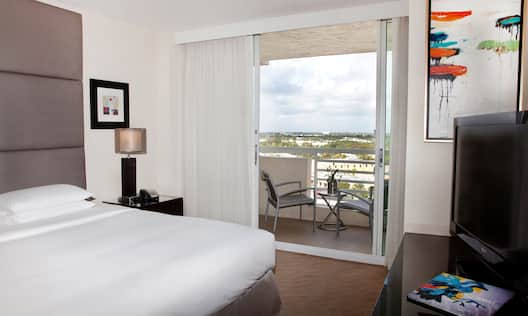 King Bed, Wall Art, Lamp on Bedside Table, Balcony Door With Open Drapes to City View, and TV in Suite