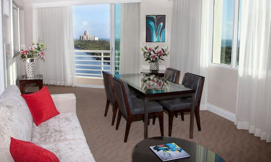 Coffee Table, Sofa Bed, Fresh Flowers on Tables, Balcony Door With Open Drapes to Water View, Wall Art, and Seating for Four at Rectangular Dining Table in Living Room Area