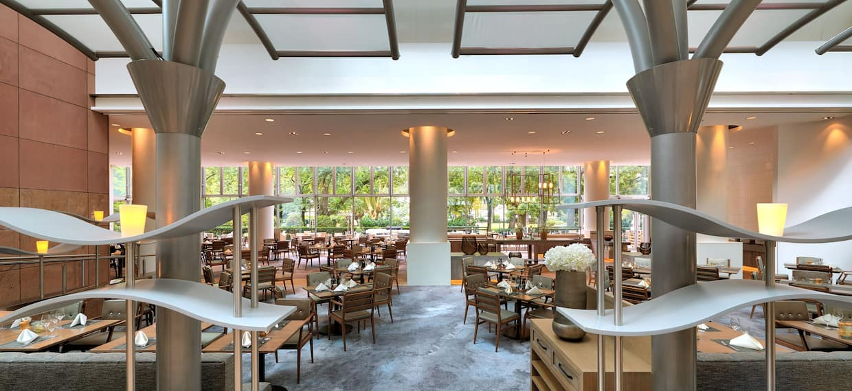 Hilton PARK Restaurant and Terrace Entrance with Tables and Chairs