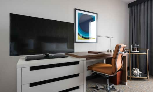 Detailed View of TV, Wall Art, Desk, and Hospitality Center in Guest Room