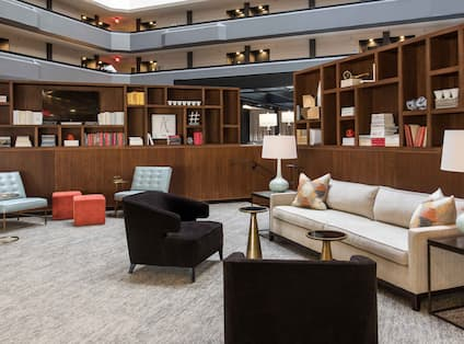 Illuminated Lamps, Tables, Wood Shelves, and Soft Seating in Lobby Lounge
