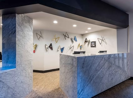 Decorative Art Behind Front Desk With Two Computer Stations