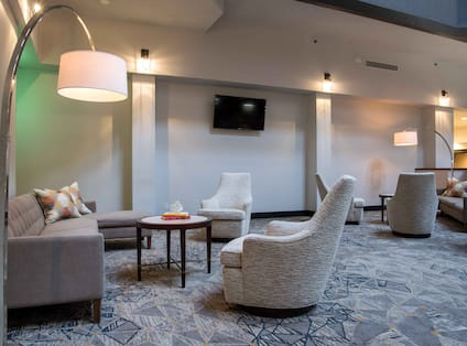 Illuminated Lamps, Tables, TV, and Soft Seating in Lobby Lounge Area
