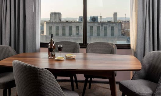 Bottle of Wine and Glasses on Table With Seating for Five by Large Window With Open Drapes in Suite Dining Area