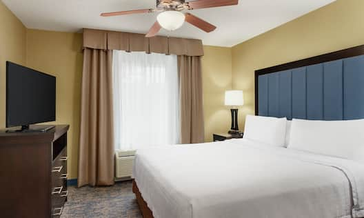 Bright private bedroom in suite featuring TV, comfortable king bed, and air conditioning unit by window.