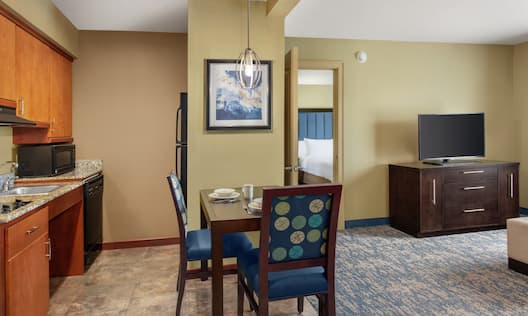 Living area in accessible suite featuring fully accessible kitchen, dining table, and lounge area with TV.