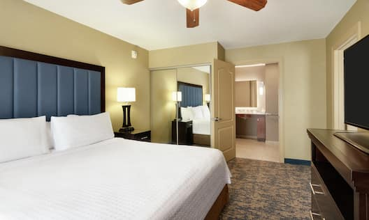 Spacious private bedroom in accessible suite featuring TV, comfortable king bed, and ensuite bathroom.