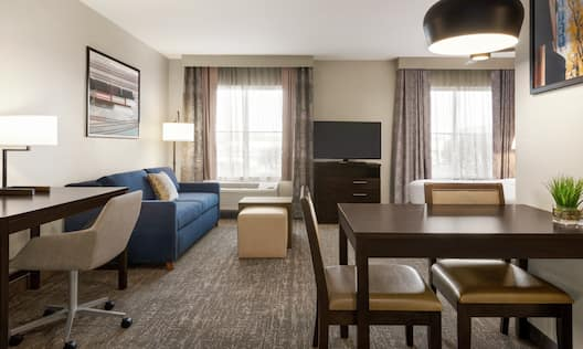 Spacious accessible suite with living area, dining table, work desk, and comfortable king bed.