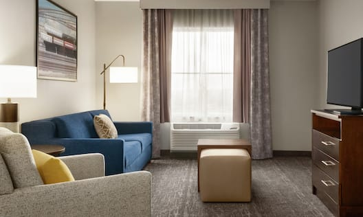 Bright living area in suite featuring sofa, chair, TV, and air conditioning unit by window.