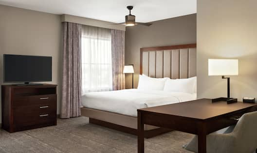 Spacious studio suite with comfortable king bed, TV, and work desk with ergonomic chair.