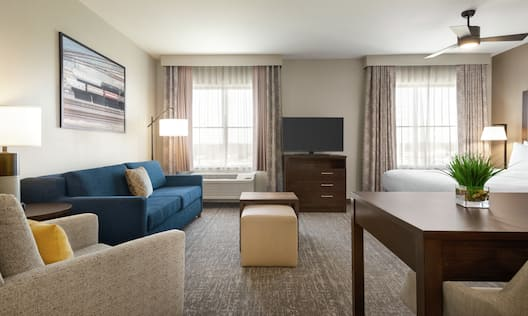 Spacious open concept suite featuring dining table, living area with sofa, TV, and comfortable king bed.